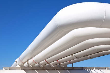 water power plant: Industrial pipe with gas and oil and water on a background of blue sky