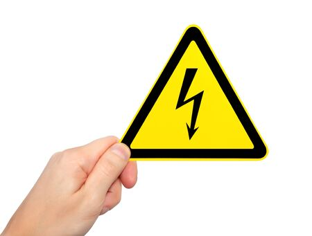 voltage symbol: isolated male hand holding yellow sign of danger high voltage symbol with lightning