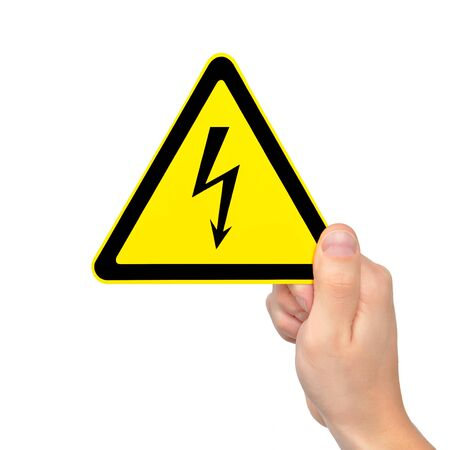 isolated male hand holding yellow sign of danger high voltage symbol with lightning photo