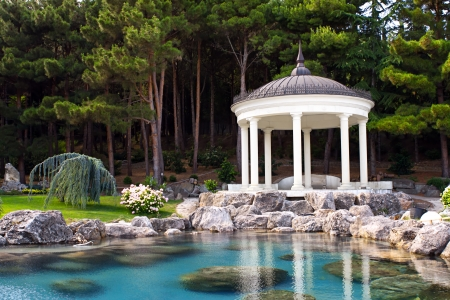 city park pavilion: gazebo by the pond in a beautiful green park Stock Photo