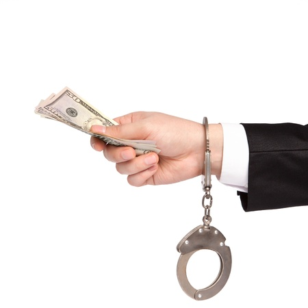 bribes: isolated hand of a businessman in a suit and handcuffs takes bribes money