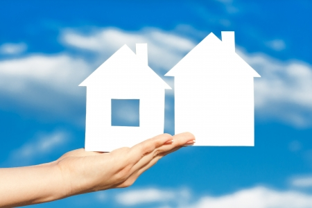 two houses on the hand on blue sky background photo