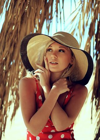 The beautiful girl in a hat under a palm tree Stock Photo - 18162613