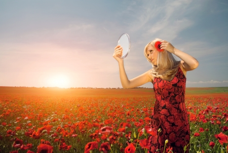 maxi dress: beautiful woman in a field of flowers looks in the mirror Stock Photo