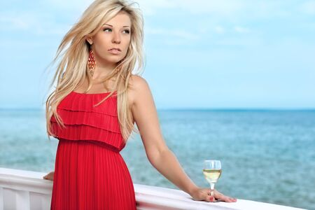 beautiful sexy girl in red dress and a glass of wine by the sea Stock Photo - 18162616