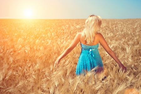 The girl in a blue dress runs on a wheaten field to the sun