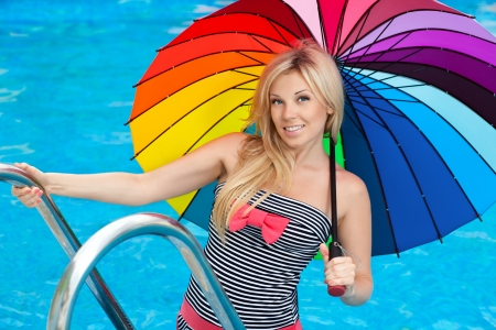 beautiful girl standing by the pool with colored umbrella and smiling Stock Photo - 18162626