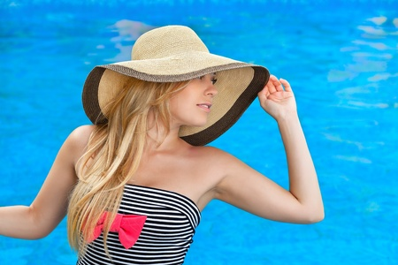 beautiful girl in the hat at the pool looks into the distance photo