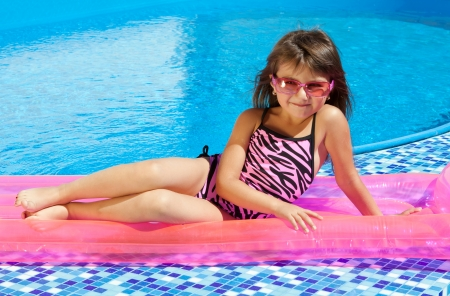 little girl on a pink mattress with a swimming pool photo