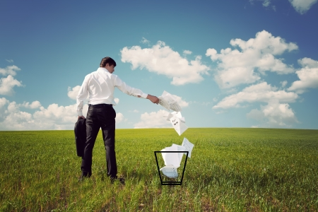 businessman in a green field with a blue sky throws papers in the trash