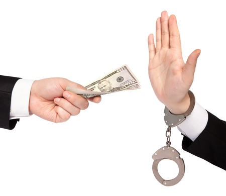 criminal activity: isolated businessman hands one gives money another in handcuffs refuses Stock Photo