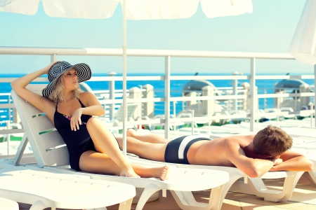 lounges: Man and woman lying on chaise lounges on a yacht in the ocean