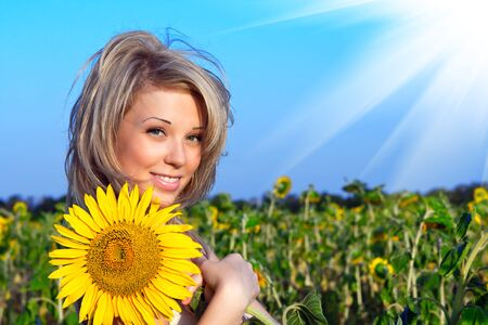 beautiful girl with a flower in the sunflower photo