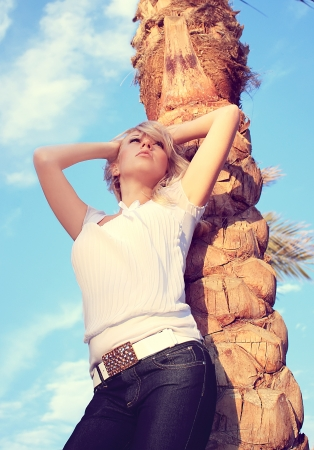 The beautiful girl under a palm tree on a beach Stock Photo - 18356278