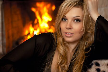 beautiful girl by the fireplace in the winter evening with glass of wine photo