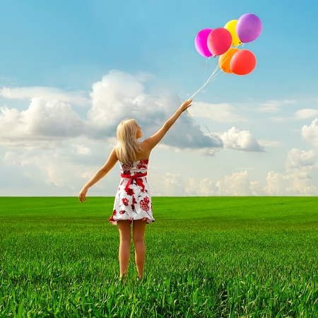 The girl with balloons plays in a field photo