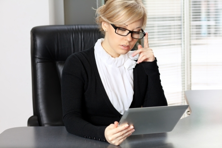 businesswoman in the office at tha table working on the tablet Stock Photo - 18380778