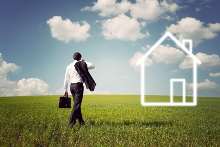businessman in a suit with a briefcase goes to the house to a spacious green field with a blue sky