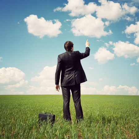 businessman in a suit standing in the field and points a finger at something photo