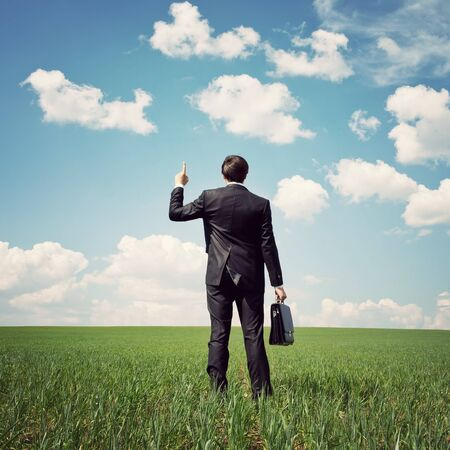 career success: businessman in a suit standing in the field and points a finger at something
