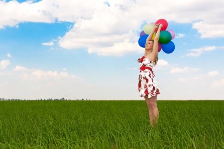 pretty girl playing with balloons in a field on holiday photo