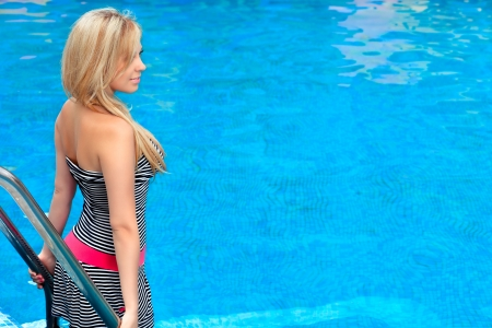 beautiful girl standing by the pool and looks into the distance Stock Photo - 18525236