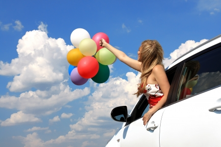 game drive: series close-up portrait of a girl in the car with colorful balloons Stock Photo