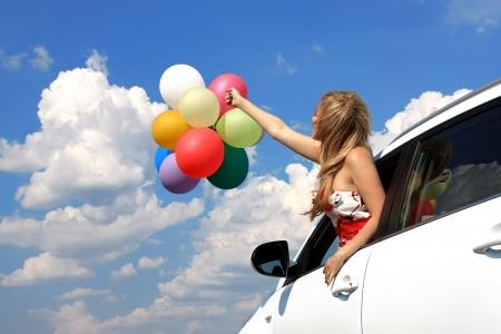 一个女孩在车里用彩色气球的特写