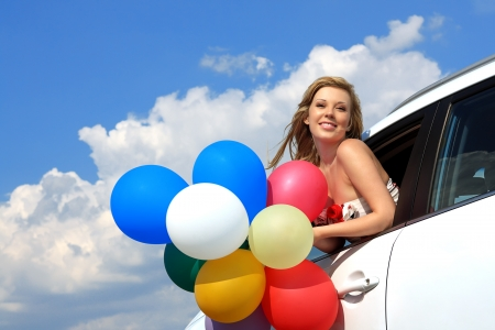 series close-up portrait of a girl in the car with colorful balloons Stock Photo