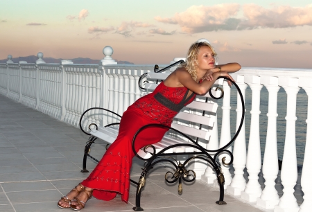 beautiful girl in evening red dress sitting on a bench on the terrace photo