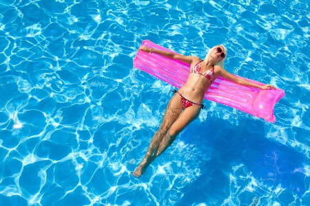 bikini pool: sexy girl floating on a mattress in the sea or swimming pool