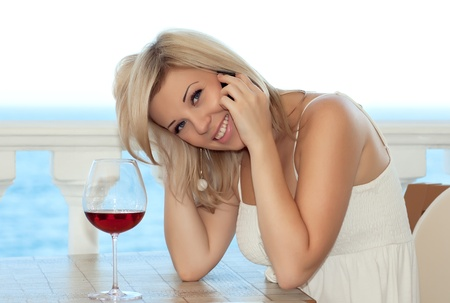 Beautiful girl talking on the phone in a cafe and drink wine Stock Photo