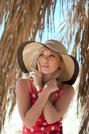 Series closeup portrait of beautiful female model in a hat under a palm tree Stock Photo - 18525189