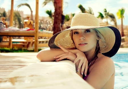 luxury hotel: The smart blonde in a hat in pool of expensive hotel Stock Photo