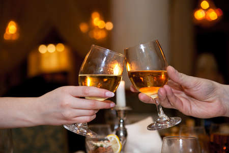 lifestyle dining: male and female hand with glasses of champagne at a festive table