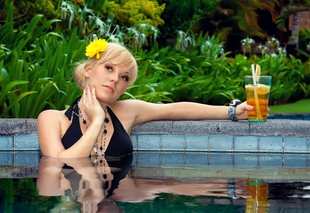 sexy girl with a cocktail in the pool