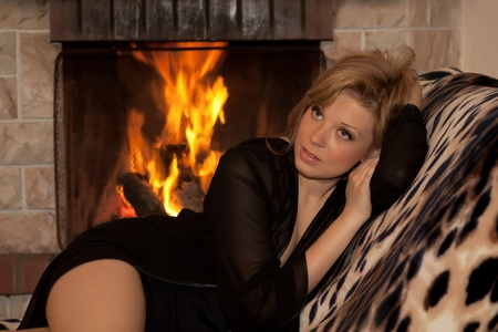 heat home: Beautiful girl lying near a burning fireplace in the cozy house