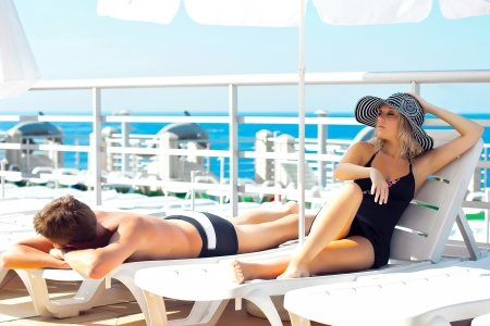 Man and woman lying on chaise lounges on a yacht in the ocean photo