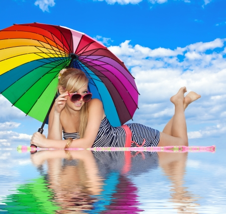 glamorous girl in retro style by color umbrella on the beach photo