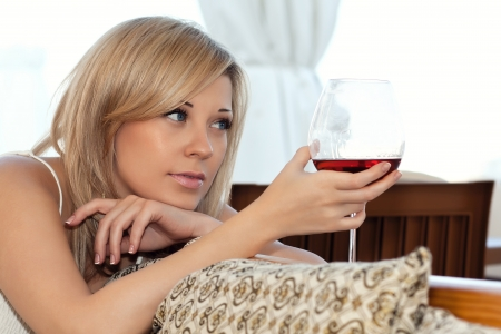 Close-up portrait of a beautiful girl in the cafe with a glass of red wine a chil photo
