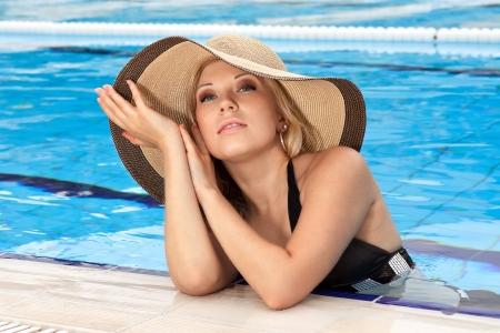 series closeup portrait the smart blonde in a hat in pool of expensive hotel photo