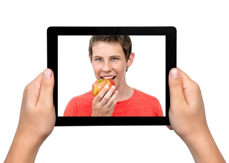 Men hands hold a tablet touch pad computer gadget with a boy and a red apple on the screen photo