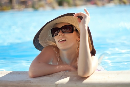 scorching: Series the smart blonde in a hat in pool of expensive hotel Stock Photo