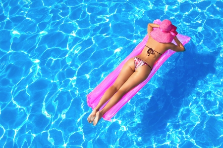 raft: sexy girl floating on a mattress in the sea or swimming pool