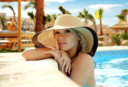 The smart blonde in a hat in pool of expensive hotel Stock Photo - 18572085