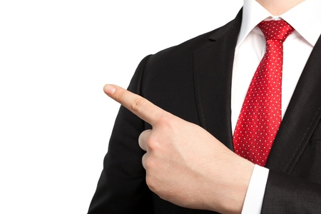 Isolated businessman in a suit and red tie points the finger at an object photo