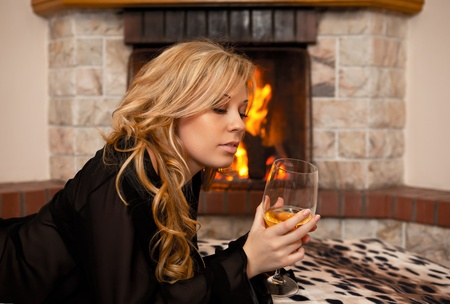 beautiful girl by the fireplace in the winter night photo
