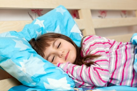 sleeping kid: beautiful little girl in pajamas sleep in bed under a blue blanket Stock Photo
