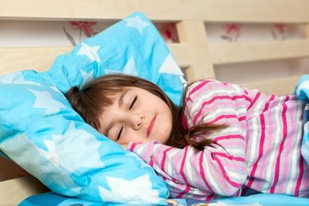enfant qui dort: belle petite fille dans le sommeil pyjama dans le lit sous une couverture bleue Banque d'images