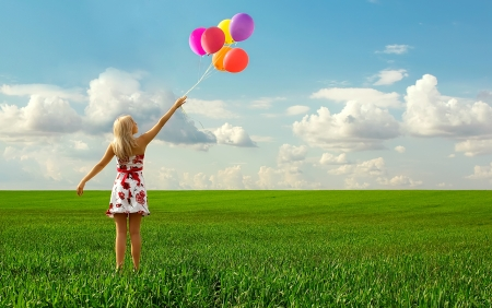 harmonous: The girl with balloons plays in a field Stock Photo